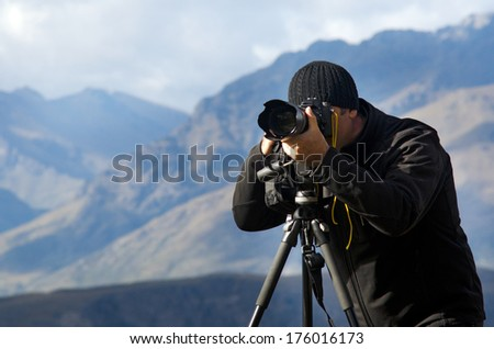 Professional travel on location and nature videographer/photographer (man) photographing and video nature and landscape outdoor. - stock photo