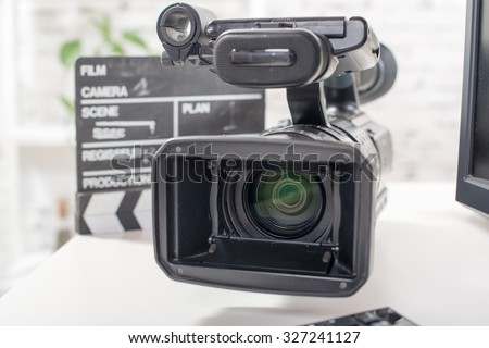 Professional video camera with a clapperboard - stock photo