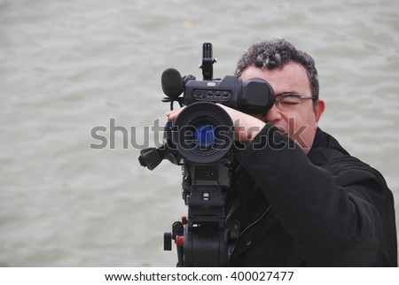 Professional videographer with camera in shooting process. Ripple water on background - stock photo