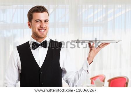 Professional waiter holding an empty dish - stock photo