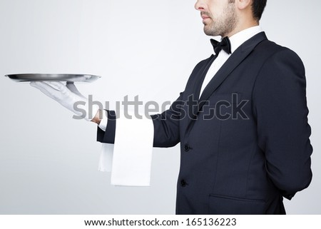 Professional waiter holding an empty silver tray over gray background - stock photo