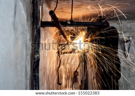 Professional welder cutting metallic pipes and grinding steel - stock photo