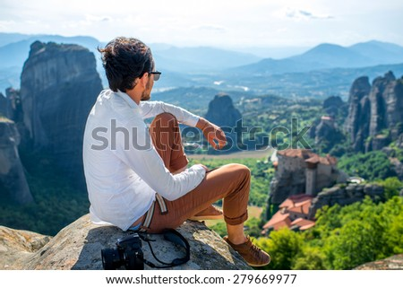 Professional well-dressed photographer sitting on the top of mountain on beautiful scenic clif background near Meteora monasteries in Greece - stock photo