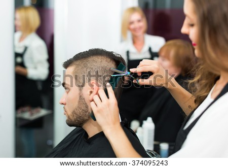 Professional woman hairdresser doing hairstyle for young men - stock photo