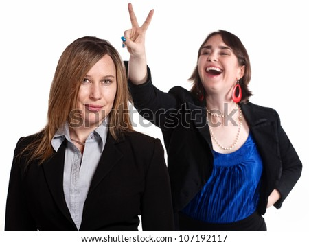 Professional woman holds rabbit ears gesture over a worker - stock photo