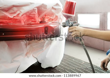 professional worker spraying red paint on a car element - stock photo