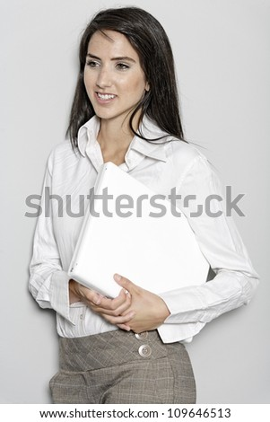 Professional working woman in corporate business trousers and shirt holding a laptop computer - stock photo