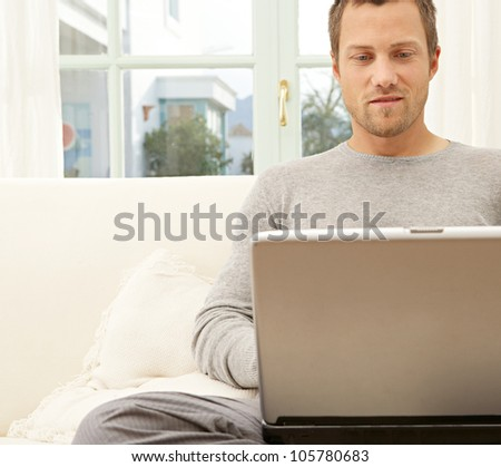 Professional young man using a laptop and a smart phone while sitting on a white sofa at home. - stock photo