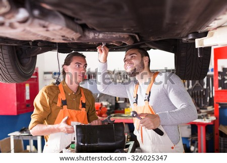 Professional young mechanics repairing car of client - stock photo
