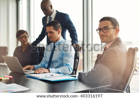 Professional young multiracial business team seated working around a table in the office with a young man in the foreground turning to look at the camera - stock photo