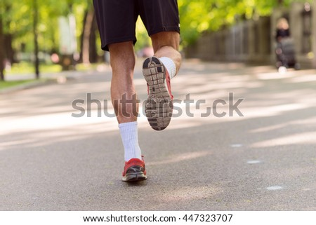 Professional young runner jogging outdoors - stock photo