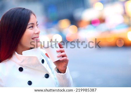 Professional young urban casual business woman in New York City Manhattan drinking coffee walking in street wearing coat downtown with yellow taxi cabs in background. - stock photo