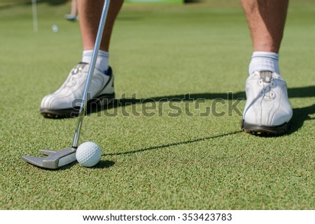 Professionals play golf. Golfer holding a a club and is going to hit the golf ball. - stock photo