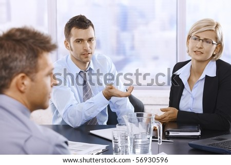 Professionals sitting at meeting table, discussing work problems in skyscraper office.? - stock photo