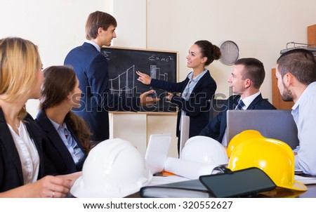 professionals with helmets and laptops having meeting in interior - stock photo
