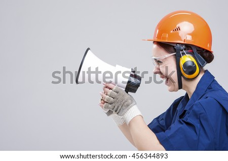 Professions Concepts.Portrait of Expressive Caucasian Female With Loudspeaker Horn Posing In Hardhat Against White. Equipped with  Coverall. Horizontal Image - stock photo
