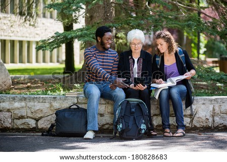 Professor helping students on campus using digital tablet - stock photo