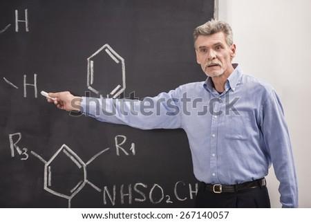 Professor of chemistry writes on the blackboard formula in University. - stock photo