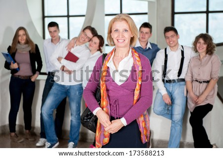 Professor posing in front of group students in hall - stock photo