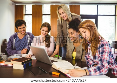 Professor teaching group of students in library at the university - stock photo