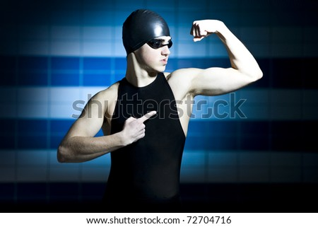 proffesional swimmer showing his muscles on blue background - stock photo