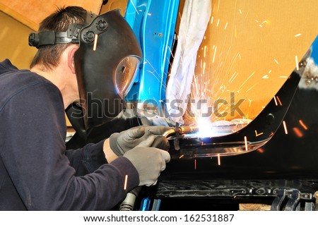 Proffesional worker welding car body. - stock photo