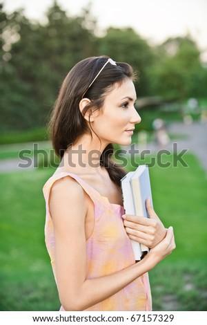 Profile girl-student holds textbooks, against summer garden. - stock photo