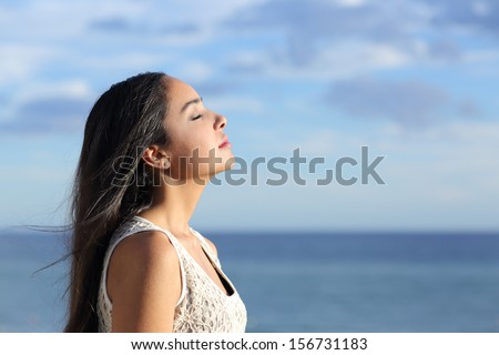 Profile of a beautiful arab woman breathing fresh air in the beach with a cloudy blue sky in the background - stock photo