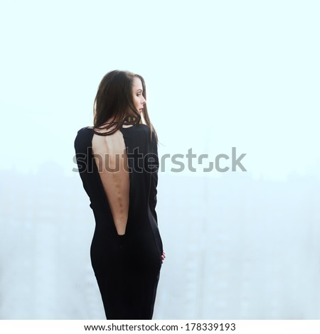 Profile of a beautiful brunette in a black dress on a blue background - stock photo