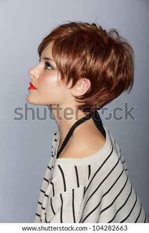profile of a beautiful woman with red lips and short feathered red hair in modern bob over studio background - stock photo