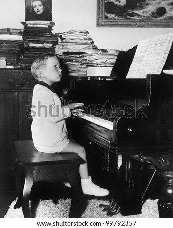 Profile of a boy sitting on a stool and playing a piano - stock photo