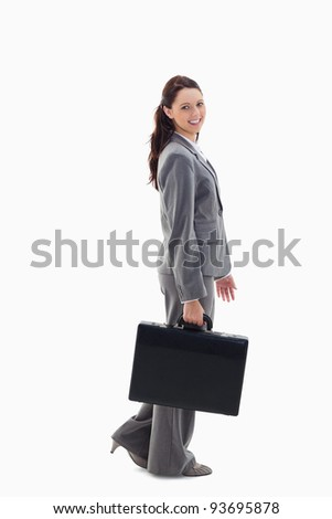 Profile of a business woman smiling and walking with a briefcase against white background - stock photo