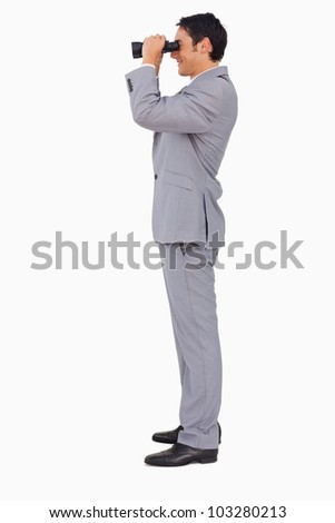 Profile of a businessman using binoculars against white background - stock photo