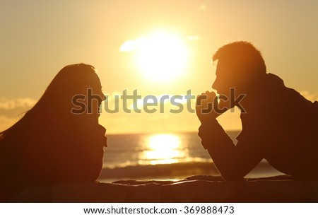 Profile of a couple silhouette looking each other at sunset on the beach with the sun in the middle and a warmth light - stock photo