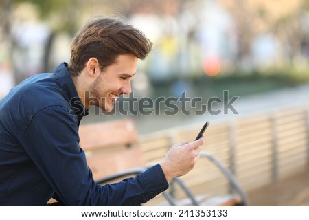 Profile of a happy guy using a smart phone sitting on a bench in a park - stock photo