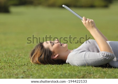 Profile of a happy woman reading a tablet reader on the grass of a park - stock photo