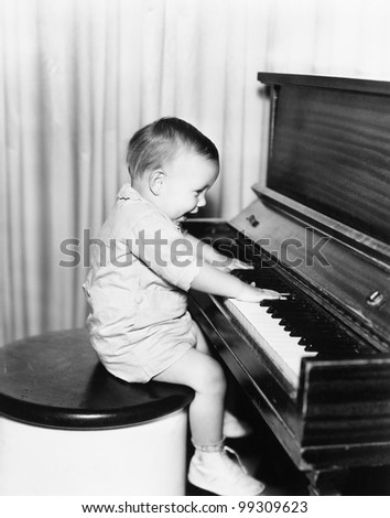 Profile of a little boy sitting on a stool and playing a piano - stock photo