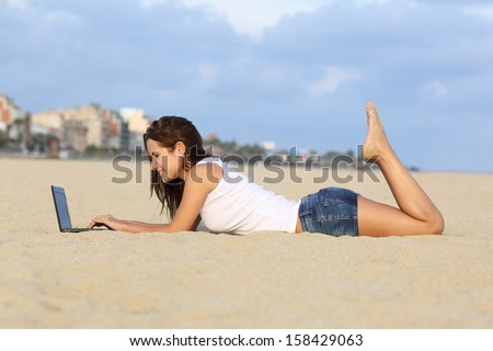 Profile of a teenager girl browsing her laptop lying on the sand of the beach with a city in the background              - stock photo
