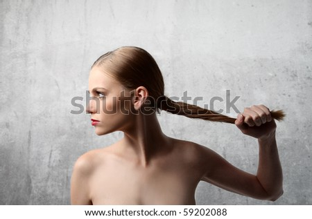 Profile of a woman holding her hair - stock photo