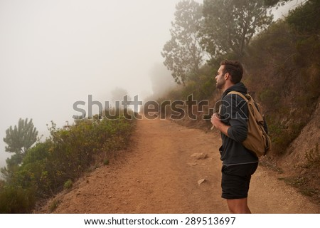 Profile of a young male hiker looking out at the view on a misty morning while on a walk on a nature trail - stock photo