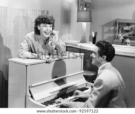 Profile of a young man playing a piano with a young woman standing in front of him and smiling and singing - stock photo