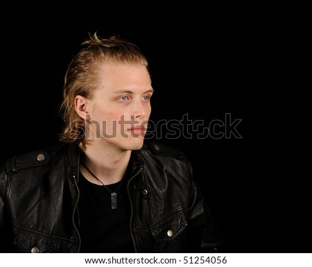 Profile of a young man with leather jacket on a black background - stock photo