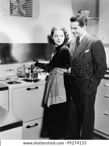 Profile of a young woman cooking food with a young man - stock photo