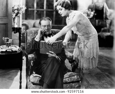 Profile of a young woman showing a book to a man sitting in an armchair - stock photo