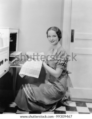 Profile of a young woman taking a pie out of the oven, smiling at the camera - stock photo