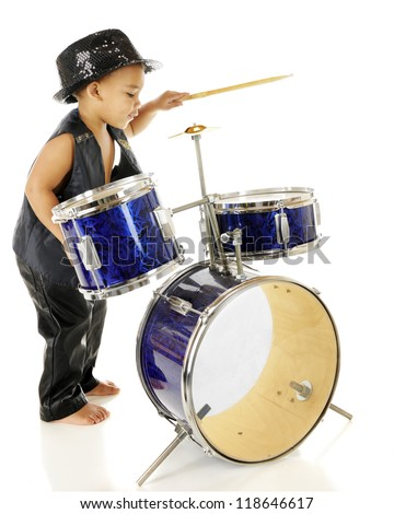 Profile of an adorable preschooler playing the drums in his sparkly fedora and black leather vest and pants.  Barefoot.  On a white background. - stock photo