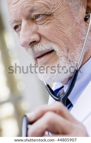 Profile of an Old Male Doctor Listing to a Stethoscope - stock photo
