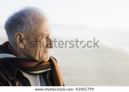 Profile of an Old Man Staring Out to The Ocean - stock photo