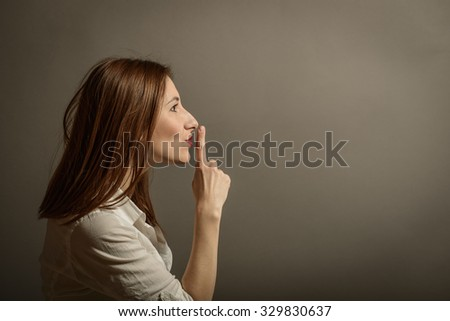 Profile of attractive business woman with finger on lips, gesturing for quiet, studio shot on gray background. Showing the silence sign.  - stock photo