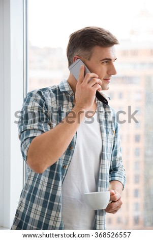 Profile of attractive man drinking coffee and talking on cellphone near the window - stock photo